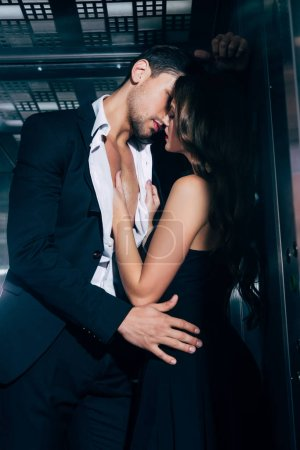 Photo for Sexy young couple passionately kissing in elevator - Royalty Free Image