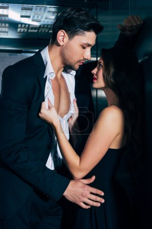 Photo for Beautiful woman passionately undressing and embracing handsome man in elevator - Royalty Free Image