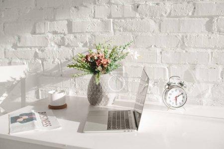 Photo pour Ordinateur portable près de journal d'affaires, de coupe et de vase avec des fleurs en cuisine - image libre de droit