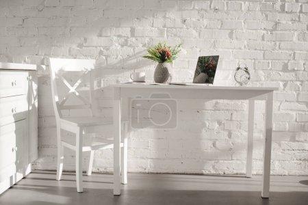 Photo pour Ordinateur portable dans la cuisine blanche près de tasse et vase avec des fleurs dans la cuisine - image libre de droit