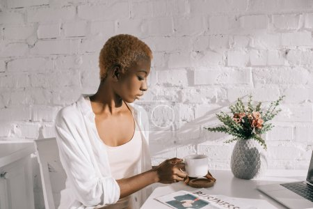 beautiful african american woman holding cup in white kitchen