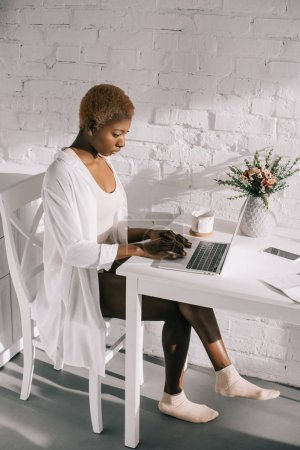 focused african american woman typing on laptop in white kitchen