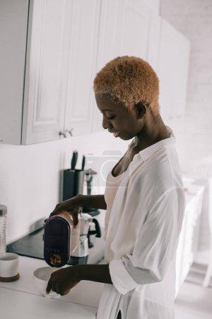 happy african american woman preparing breakfast in white kitchen