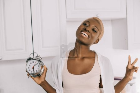 cheerful african american woman holding clock and showing peace sign