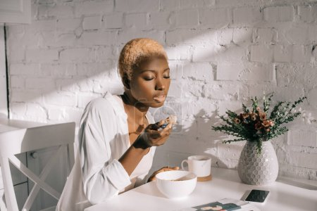 beautiful african american woman eating cornflakes in white kitchen