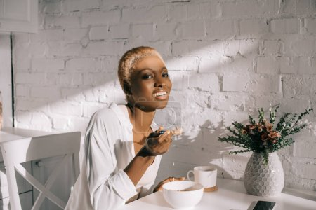 cheerful african american woman holding spoon with cornflakes and smiling in kitchen