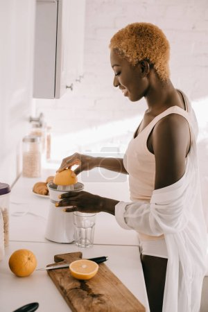 Photo for Side view of attractive african american woman squeezing orange - Royalty Free Image