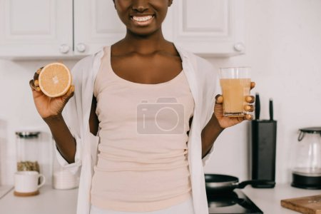 cropped view of african american woman showing glass of orange juice and half of orange