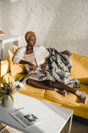 Photo pour Confiante femme afro-américaine, couché sur le canapé jaune dans le salon - image libre de droit