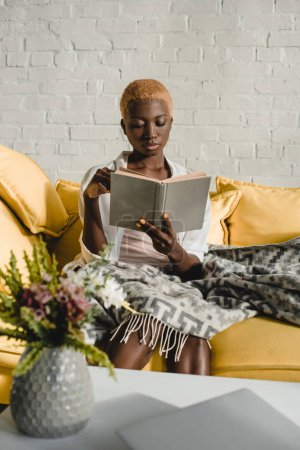 attractive african american woman reading book on yellow sofa