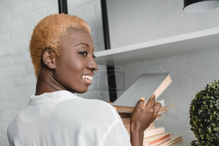 cheerful african american woman taking book from rack