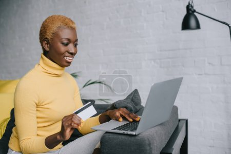 attractive african american woman using laptop and holding credit card