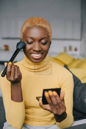 smiling african american woman applying powder with cosmetic brush