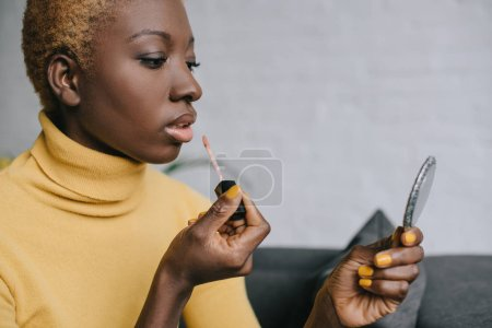 pensive african american woman applying lip gloss and looking in mirror