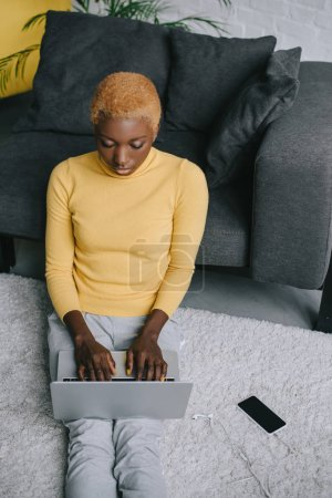 african american woman sitting on carpet and using laptop