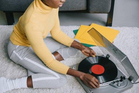 Photo pour Vue recadrée de la femme afro-américaine en utilisant un tourne-disque sur le tapis - image libre de droit