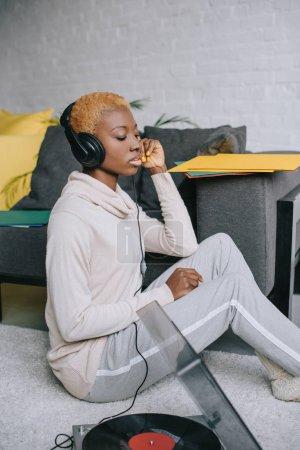 Photo pour Femme afro-américaine assis sur le tapis et en écoutant la musique au casque - image libre de droit