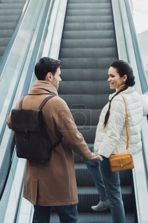 smiling couple in warm clothing holding hands and going up on escalator