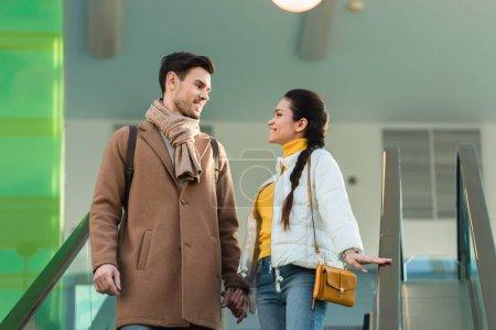 Photo pour Beau couple tenant la main, se regardant et descendant sur l'escalator - image libre de droit