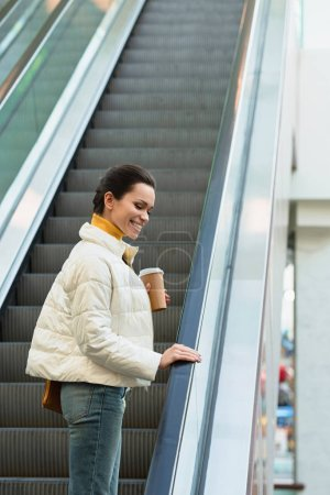 beautiful girl smiling, going up on escalator and holding disposable cup