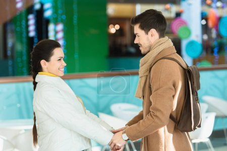 loving couple smiling, holding hands and looking at each other