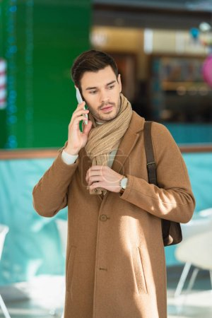 disappointed man in warm clothing talking on smartphone