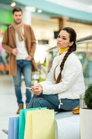 Photo pour Jolie jeune fille tenant smartphone et assis sur un banc avec des sacs de shopping au centre commercial - image libre de droit