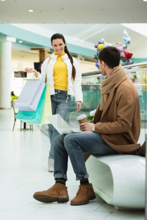 handsome man with laptop sitting on bench, holding disposable cup and looking at girl with shopping bags in mall