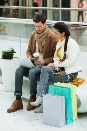 Photo pour Bel homme avec tasse en papier et fille avec smartphone assis sur le banc et regardant l'écran d'ordinateur portable dans le centre commercial - image libre de droit