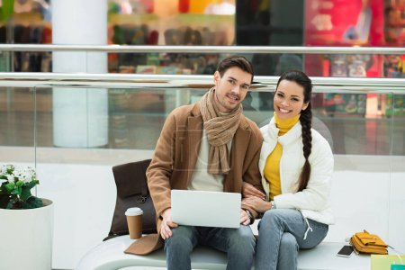 handsome man with laptop and beautiful girl sitting on bench and looking at camera in shopping mall