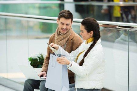 Photo pour Homme souriant avec ordinateur portable et fille avec sac à provisions assis sur le banc et regardant les achats dans le centre commercial - image libre de droit