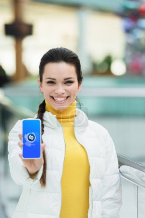 beautiful girl smiling, looking at camera  and showing smartphone screen with shazam app