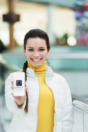 smiling girl looking at camera and showing smartphone screen with uber app