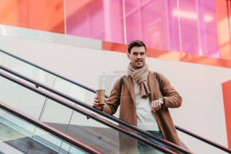 Photo pour Bel homme dans des vêtements chauds, tenant le gobelet jetable, souriant et en regardant la caméra sur l'escalator - image libre de droit