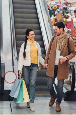 Photo pour Bel homme avec une tasse de papier et de la jolie fille de sacs à main dans la main et en regardant l'autre près d'escalator - image libre de droit