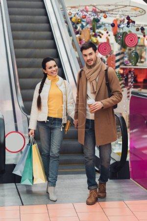 Photo pour Jolie fille de sacs à main dans la main avec bel homme regardant la caméra près d'escalator - image libre de droit