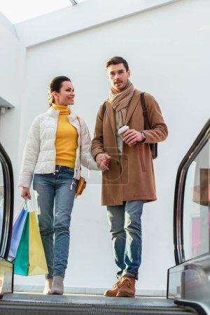 Photo pour Couple d'amoureux avec des sacs à provisions et gobelet jetable en haut de l'escalator - image libre de droit