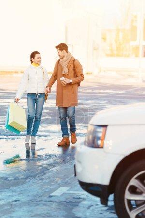 Photo pour Couple d'amoureux avec des sacs à provisions et gobelet jetable tenant par la main et en passant par un parking - image libre de droit