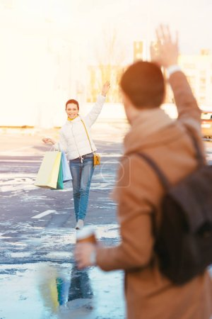 attractive girl with shopping bags waving with hand to boyfriend in parking