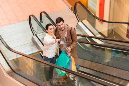 Foto de Hombre guapo con bolsas y chica atractiva con vaso desechable apuntando con el dedo en la escalera mecánica - Imagen libre de derechos