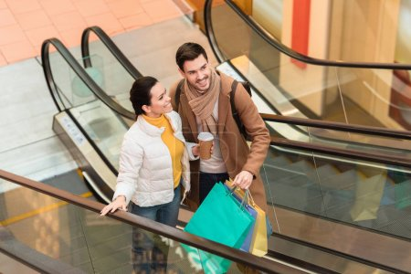 Photo for Smiling man holding shopping bags and attractive girl with disposable cup on escalator - Royalty Free Image
