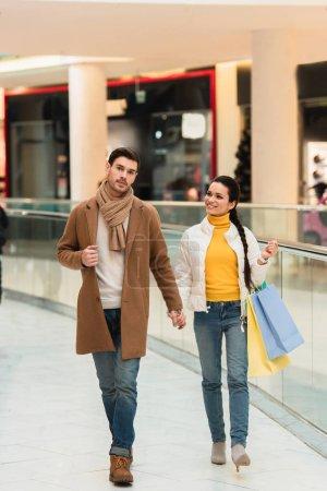 Photo pour Bel homme avec tasse en papier et jolie fille avec des sacs à provisions dans le centre commercial - image libre de droit