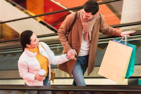 Photo pour Homme souriant avec des sacs à provisions et belle fille avec tasse jetable en se regardant sur l'escalator - image libre de droit