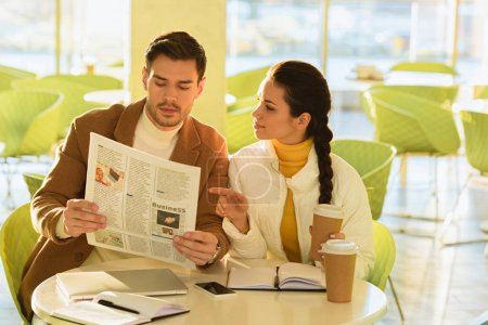 handsome man and attractive girl reading business newspaper in cafe