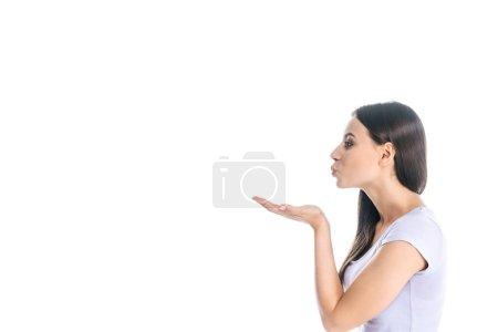 Photo pour Vue latérale de jeune belle femme soufflant baiser isolé sur blanc - image libre de droit