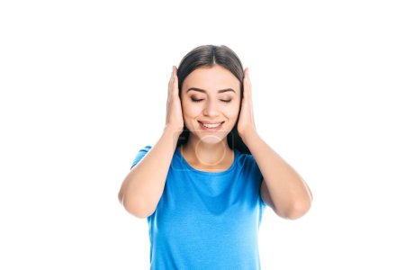 portrait of attractive smiling woman covering ears with hands isolated on white