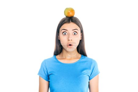 portrait of shocked young woman with fresh apple on head isolated on white
