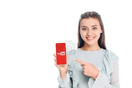 smiling woman showing smartphone with youtube logo isolated on white