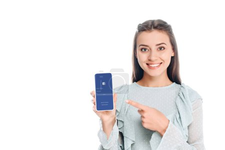 smiling woman showing smartphone with facebook logo on screen isolated on white
