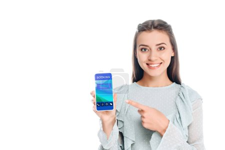 Photo for Smiling woman showing smartphone with booking lettering isolated on white - Royalty Free Image